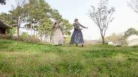 Two young cheerful women dancing in the park wearing traditional Korean dresses. Traveling South Korea stock video footage