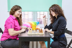 Two young cheerful women playing chess together Stock Image