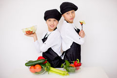 Two young chefs evaluate a salad isolated. Two young chefs near the white table evaluate a salad isolated Stock Photos