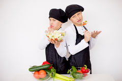 Two young chefs evaluate a salad isolated. Two young chefs near the white table evaluate a salad isolated. disgusting Stock Images