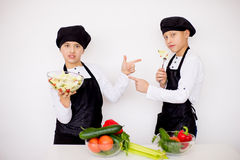 Two young chefs evaluate a salad isolated. Two young chefs near the white table evaluate a salad isolated. point each other Royalty Free Stock Photo