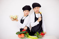 Two young chefs evaluate a salad isolated. Two young chefs near the white table evaluate a salad isolated. taste Stock Photography
