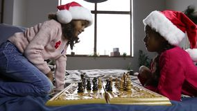 Two young chess players in santa hats indoors. Smart small african american girls in santa hats playing chess on bed in domestic interior. Lovely serious sisters stock video footage