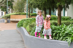 Two young child girls walking by street in auckland Royalty Free Stock Images