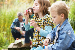 Two Young Children Blowing Bubbles outisde royalty free stock photography