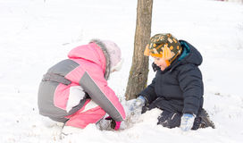 Two young children digging in the snow Royalty Free Stock Image