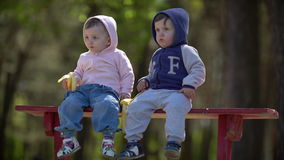 Two young children eating bananas sitting on the bench. Outdoors stock footage
