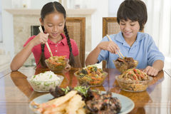 Two young children eating chinese food. In dining room Stock Images