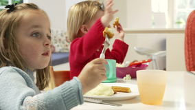 Two Young Children Eating Meal At Home. Two girls sitting at table eating meal together.Shot on Sony FS700 in PAL format at a frame rate of 25fps stock video footage