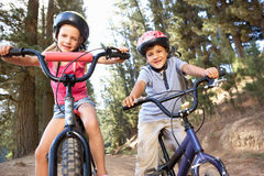 Two young children enjoying a bike ride. Smiling at camera stock images