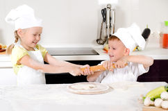 Two young children fighting over a rolling pin Stock Photos