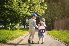 Two young children friends boy and girl hold hands and walk along road in summer green park on sunny afternoon. Child friendship. Two young children friends boy royalty free stock photography
