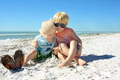 Two Young Children Hugging on the Beach Stock Image