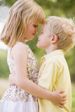 Two young children hugging outdoors Royalty Free Stock Images
