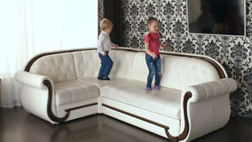 Two young children jumping on a big white sofa. Two young children jumping on a big white sofa, slow motion stock video