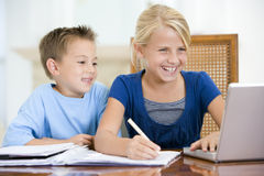 Two young children with laptop doing homework Royalty Free Stock Photo