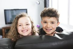 Two young children in living room with flat screen Stock Image