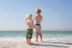 Two Young Children Looking Out Over Ocean on Beach Royalty Free Stock Photos