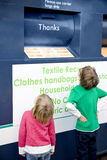 Two young children looking at a recycling container for textiles Stock Images