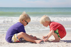 Two Young Children Playing in Sand on Beach by Ocean. Two young boy children are sitting on the white sand beach, digging a hole with their hands to build a Stock Photo