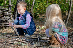 Two young children playing with sticks outdoors royalty free stock photos
