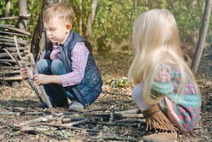 Two young children playing with sticks outdoors Royalty Free Stock Image