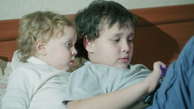 Two young children playing with a tablet. Computer as they relax together on a sofa with the older brother surfing the internet stock video footage