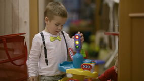 Two young children playing with their toys. Two cute young preschool children playing with their toys with a toy traffic light and colourful plastic accessories stock footage