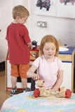 Two Young Children Playing Together at Montessori/ Stock Image