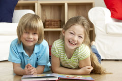 Two Young Children Reading Book at Home. Looking Cheerful Stock Photo