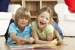 Two Young Children Reading Book at Home. Having Fun Stock Images