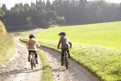 Two young children ride bicycles in park royalty free stock image