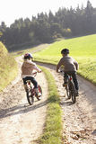 Two young children ride bicycles in park Stock Images