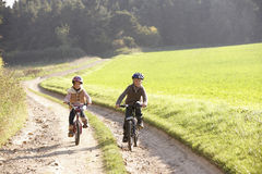 Two young children ride bicycles in park Royalty Free Stock Photography