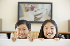 Two young children in room with flat screen Stock Photos