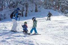 Two young children, siblings brothers, skiing in Austrian mountains on a sunny day. Wintertime, enjoying sports royalty free stock photos