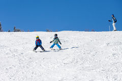 Two young children, siblings brothers, skiing in Austrian mounta Royalty Free Stock Photo