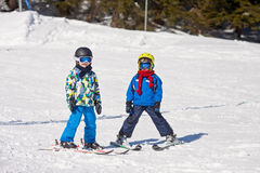 Two young children, siblings brothers, skiing in Austrian mounta Stock Photo