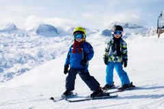 Two young children, siblings brothers, skiing in Austrian mounta Royalty Free Stock Photography