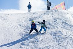 Two young children, siblings brothers, skiing in Austrian mountains on a sunny day. Wintertime, enjoying sports stock images