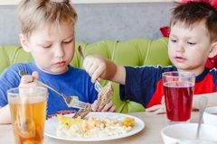 Two young children sit at the table and eat pasta with a cutlet stock photo