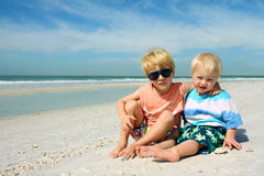 Two Young Children Sitting on Beautiful Beach stock images