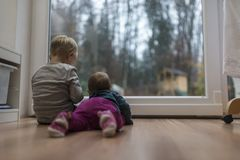 Two young children sitting at a glass door. Two young children sitting and lying on the wooden floor in front of a glass door Stock Photo