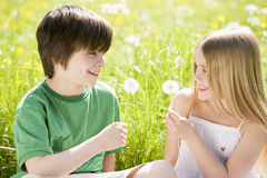 Two young children sitting outdoors Stock Photos