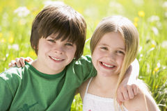 Two young children sitting outdoors arm in arm royalty free stock photo