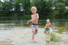 Two Young Children Swimming and Playing in Lake Stock Images