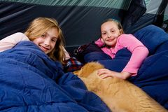 Two young children in a tent with sleeping bags. Two young girls in a tent camping in sleeping bags with a puppy Stock Photography