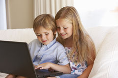 Two Young Children Using Laptop At Home Stock Photography