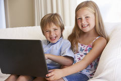 Two Young Children Using Laptop At Home Stock Images