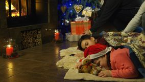 Two young children waiting for Santa Claus. Asleep on the floor in front of the Christmas tree with the parents entering to place rugs over them and lay out the Stock Photo